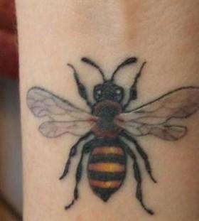Wrist yellow bee tattoo on arm