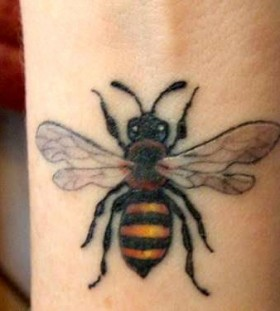 Yellow and black bee tattoo on arm