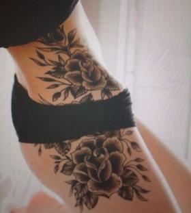 Black flowers girl's hip tattoo