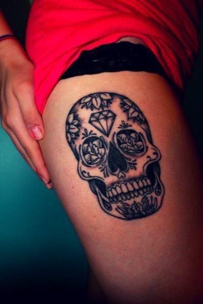 Skull and black diamond tattoo on leg