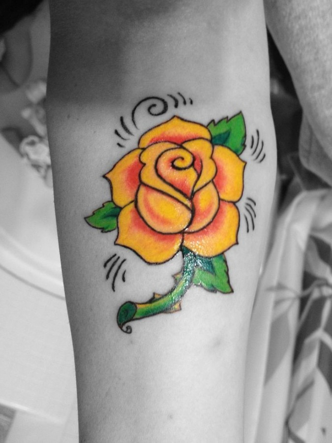 Black and white style photo with yellow rose tatoo