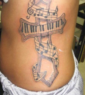 Cross and scary music note tattoo