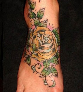 Green leafs and yellow rose tattoo