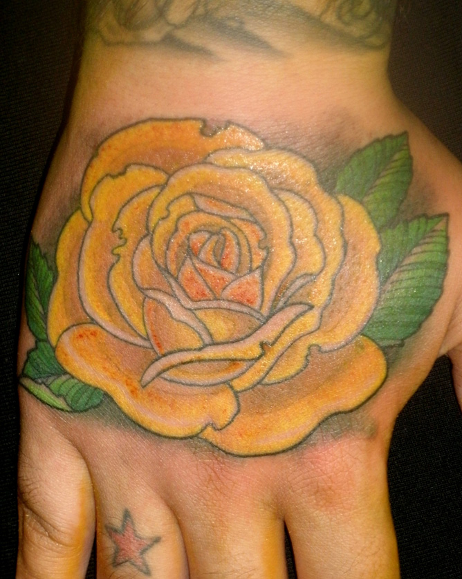 Small red star's and yellow rose tattoo