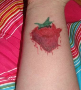 Smashed strawberry tattoo on wrist