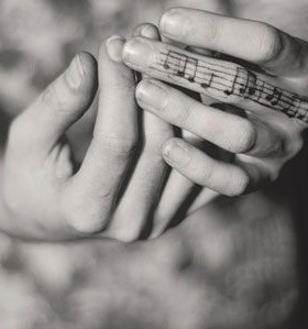 Hand's and black music note tattoo