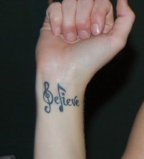 Wrist believe and music note tattoo