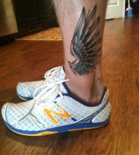 Black simple wing tattoo on leg