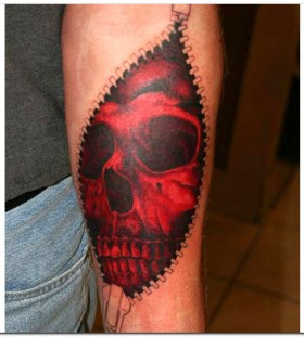 Arm's zipper and red skull tattoo