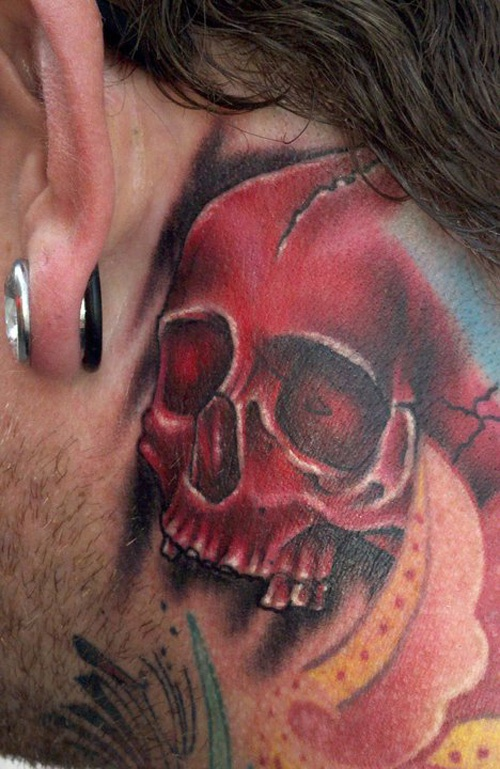 Men's ear and red skull tattoo