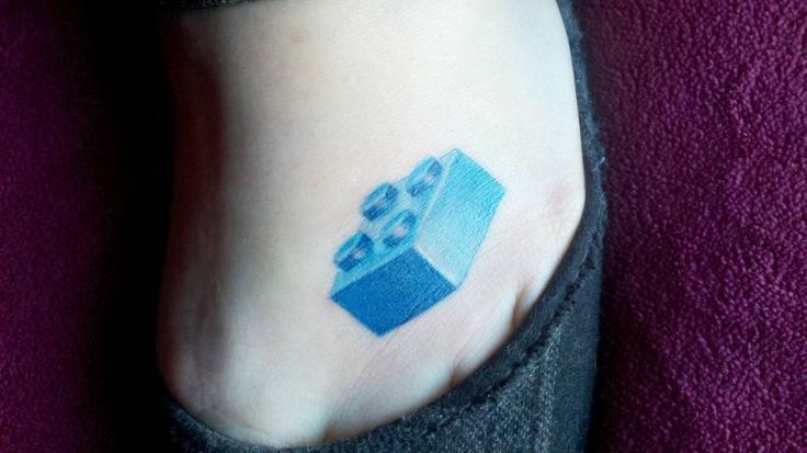 Blue lego brick tattoo on foot