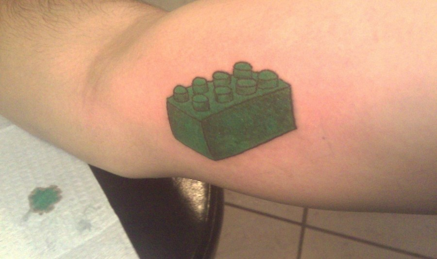 Green lego brick tattoo on arm
