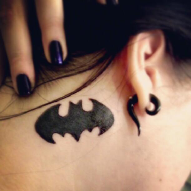 Batman logo tattoo behind the ear