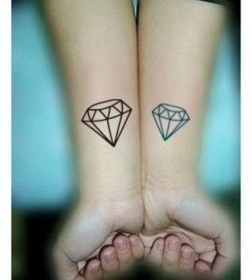 Black and blue diamond tattoo on arm