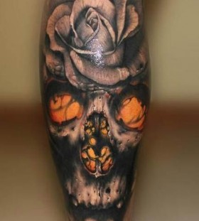 Black skull with yellow eyes and rose tattoo