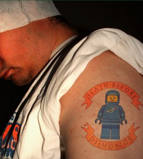Blue lego man tattoo on arm