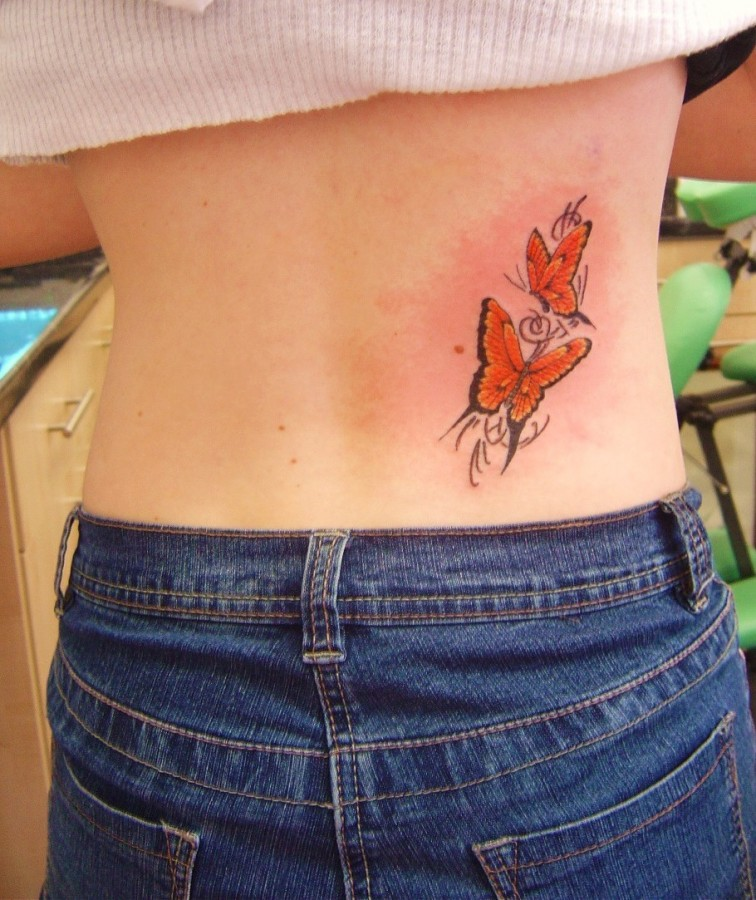 Girl's back red butterfly tattoo