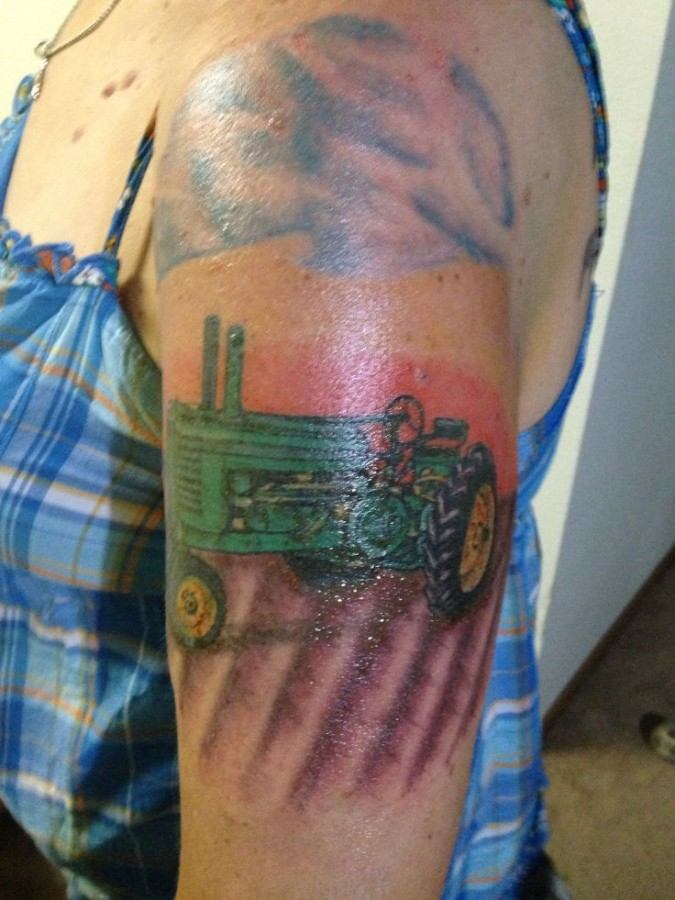 Green tractor tattoo on arm