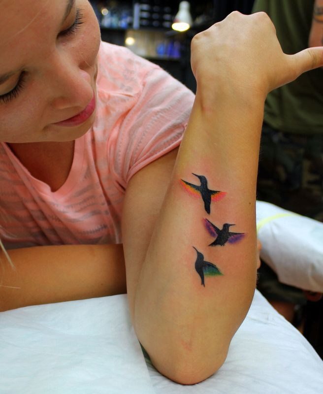 Colorful lovely birds tattoo on arm