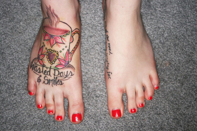 Teacup and writing foot tattoo