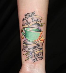 Teacup and writing tattoo