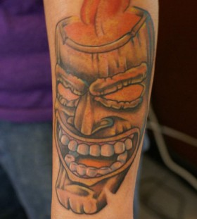 Tiki mask arm tattoo