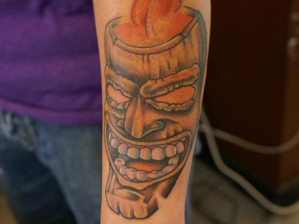 Tiki mask arm tattoo