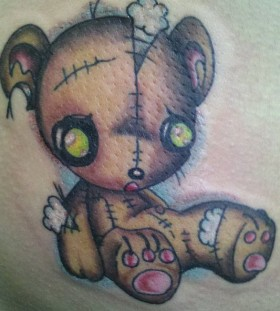 Torn teddy bear tattoo