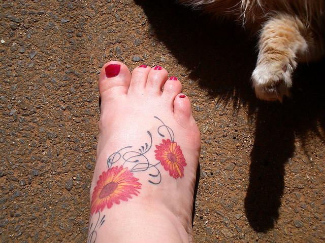 Beautiful Swirly Red Daisy Flower Foot Tattoo Design for Women