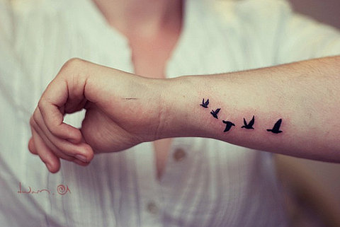 Design Of Flying Bird Silhouette Tattoo On Arm