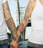 Tattooed Hispanic Couple Holding Hands