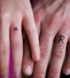 R and a Shaped Tattoo Design on Ring Finger