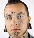 Man With Neck and Face Tattoos And Ear Piercings